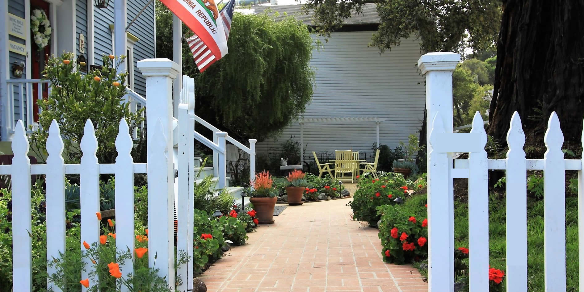 olallieberry inn gardens and gate into the bed and breakfast with flags flying