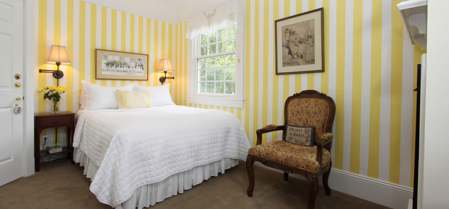 cambria bed and breakfast guestroom - bed with yellow striped wall paper and sitting chair